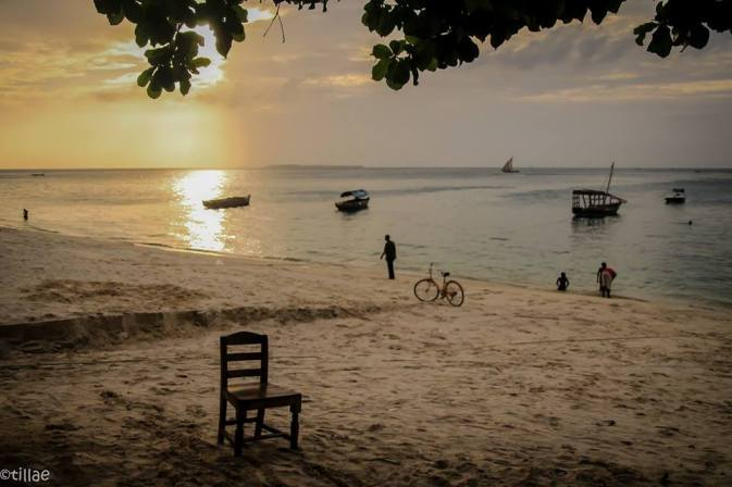 Still life with a chair and sunset on the beach ...